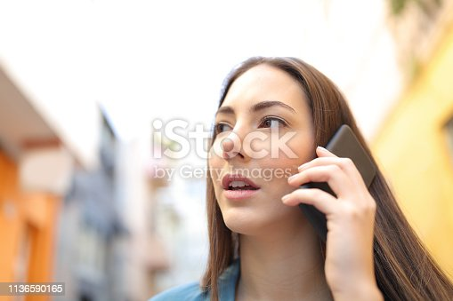 Woman talking on phone while is walking in the street