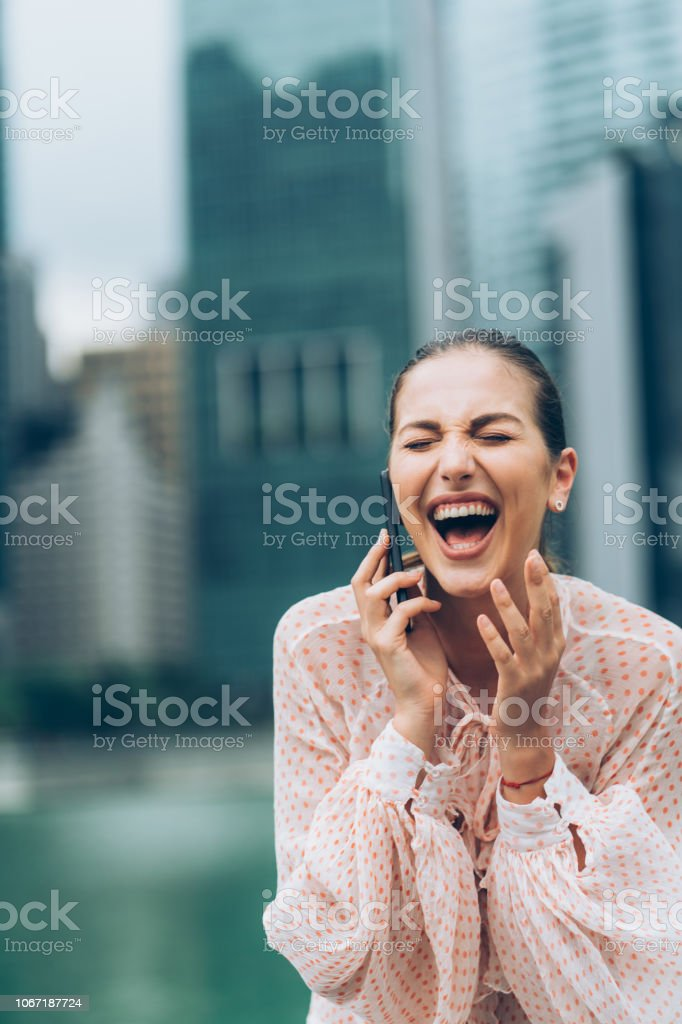Woman talking on the phone and laughing out loud