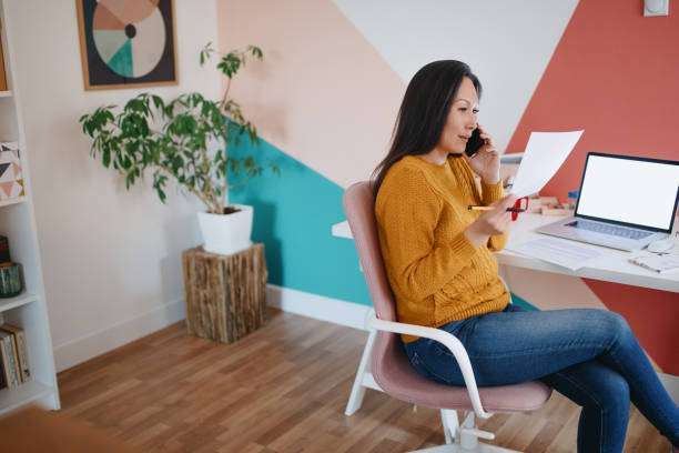 Woman talking on the phone in home office stock photo
