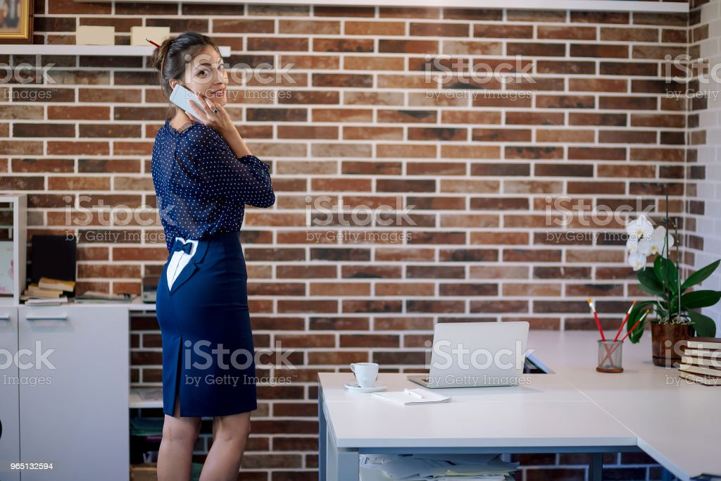 Woman talking on the phone in office royalty-free stock photo