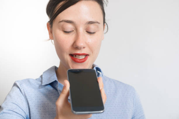 Woman talking on the phone with digital voice assistant stock photo