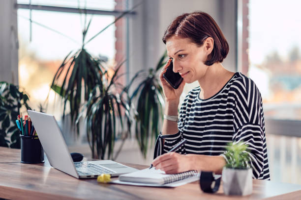 Woman talking on the smart phone in the office Woman talking on the smart phone and writing notes in notebook in the office telecommuting stock pictures, royalty-free photos & images