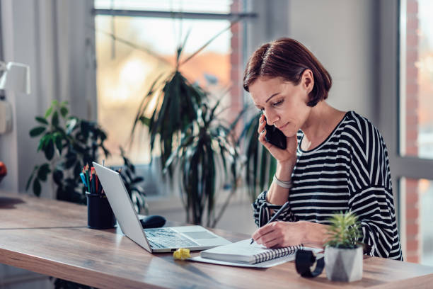 Woman talking on the smart phone in the office stock photo