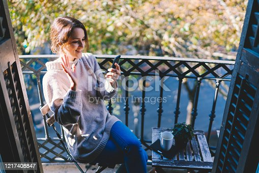 Positive woman staying at the terrace with morning coffee and enjoying to talk with a friend on video call. Covid-19 pandemic, people are social distancing and meeting online.