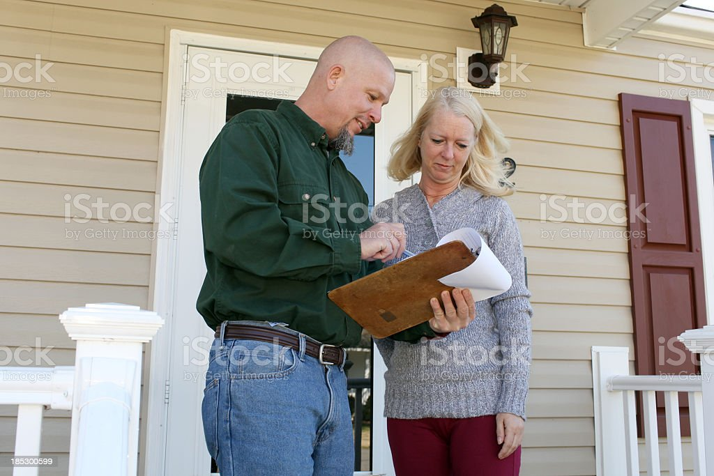 A woman talking to a home inspector on her front porch stock photo