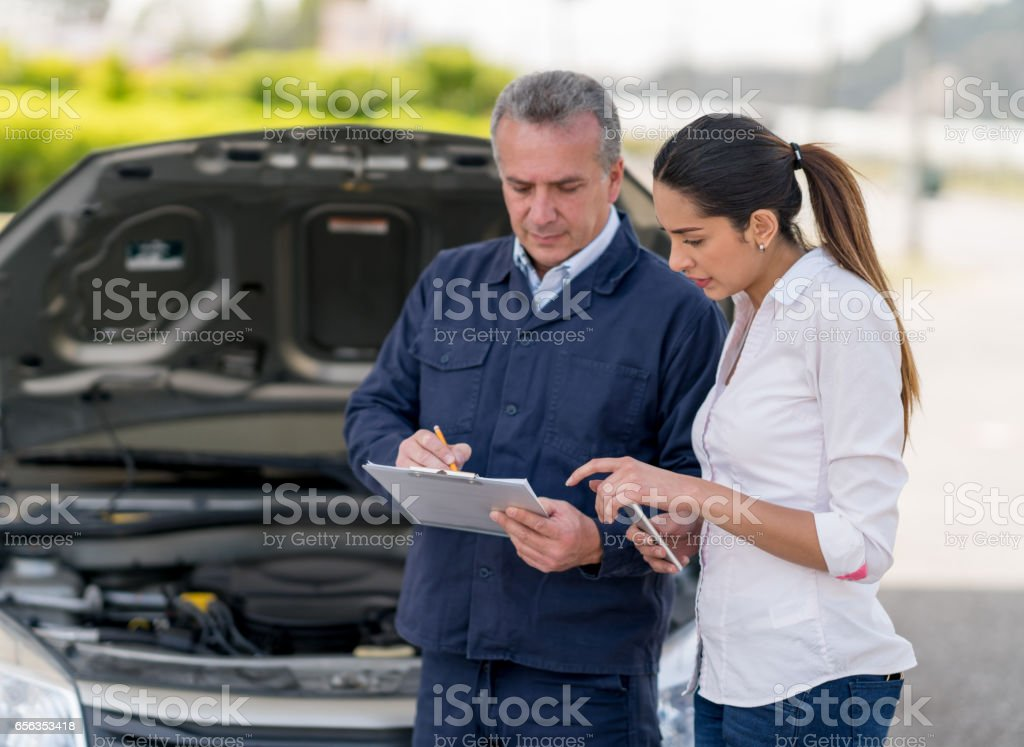 Woman talking to a mechanic about her car stock photo