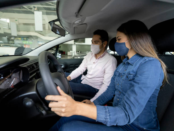 Woman talking to a salesman and wearing facemasks while buying a car at the dealership stock photo