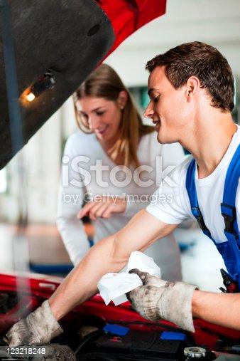 136591855 istock photo Woman talking to car mechanic in repair shop 123218248