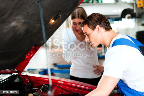 136591855 istock photo Woman talking to car mechanic in repair shop 123218250