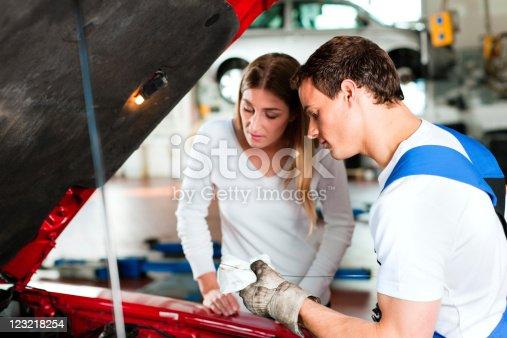 136591855 istock photo Woman talking to car mechanic in repair shop 123218254