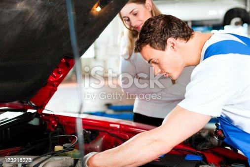 136591855 istock photo Woman talking to car mechanic in repair shop 123218273