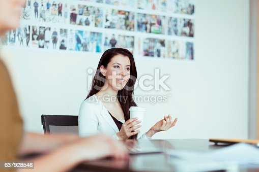1063657732 istock photo Woman talking to colleagues in design studio office meeting 637928546
