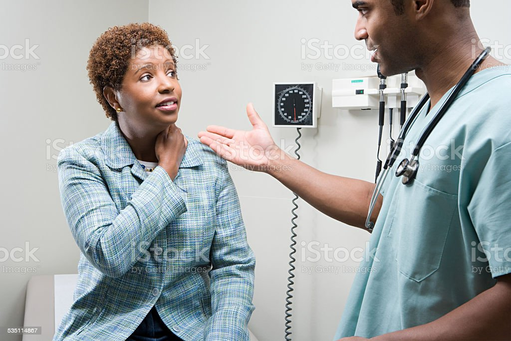 Woman talking to doctor stock photo
