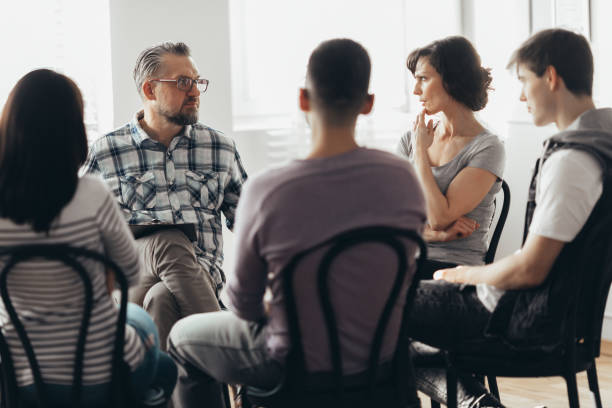 Woman talking to professional psychotherapist in support group for ACOA stock photo