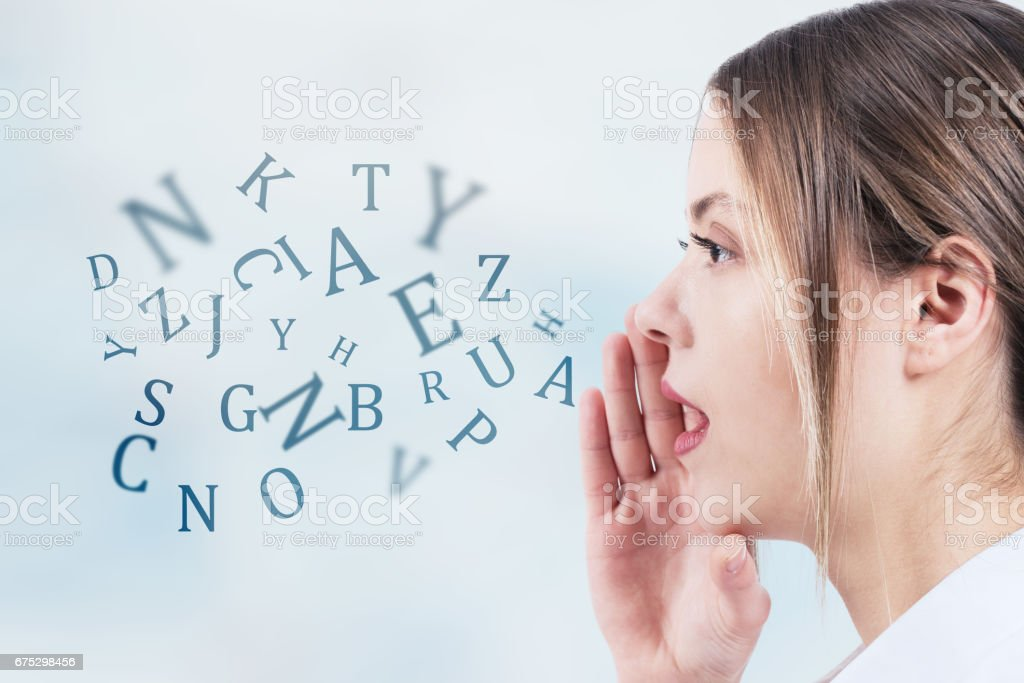 Woman talking with alphabet letters coming out of her mouth. Communication concept stock photo