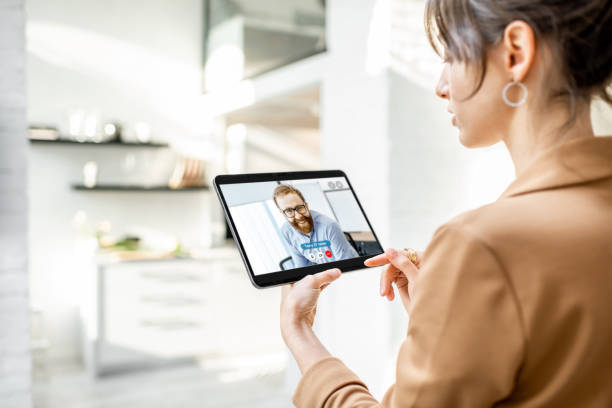 Woman talking with coworker using digital tablet stock photo