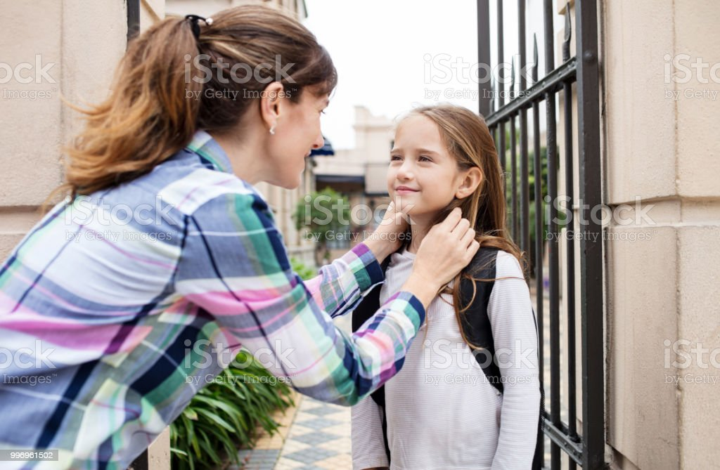 Woman talking with daughter outside school gate stock photo