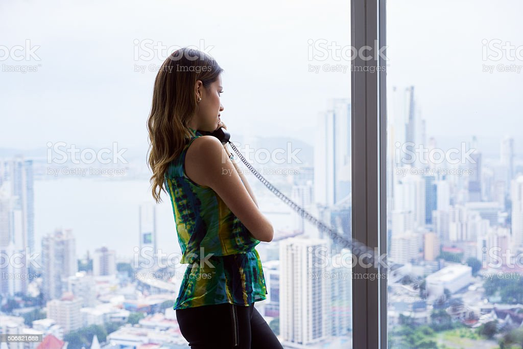 Woman Talking With Wired Telephone In Office Looking Outside Win stock photo