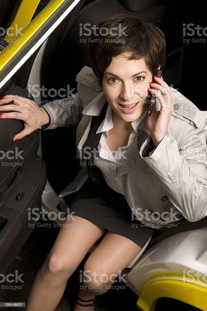 Woman Talks on Cell Phone as She Exits the Taxi royalty-free stock photo