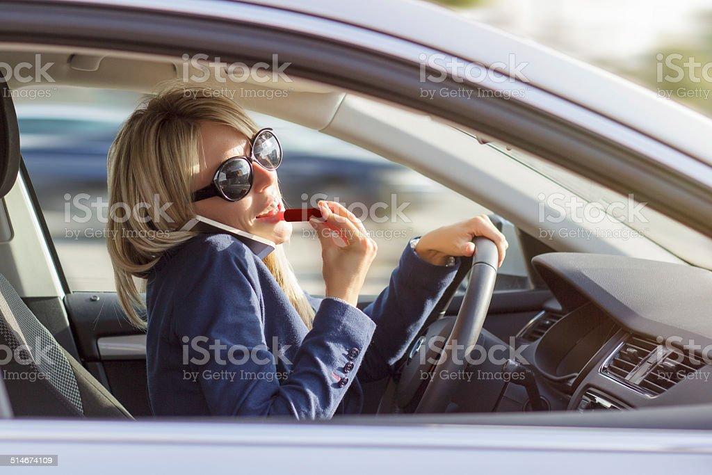 Mulher fala pelo telefone e a maquiagem enquanto estiver dirigindo carro - foto de acervo