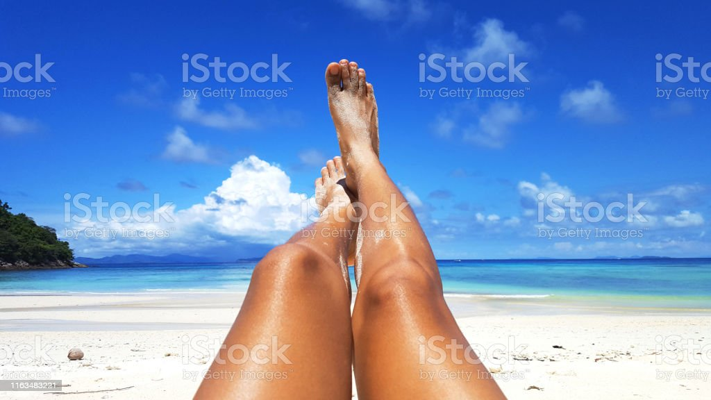 Woman tanned skin legs on the beach. Woman tanned skin legs sunbathing on the white sand beach with the blue sky and sea in the background, Summer holidays and vacations concept. Adult Stock Photo