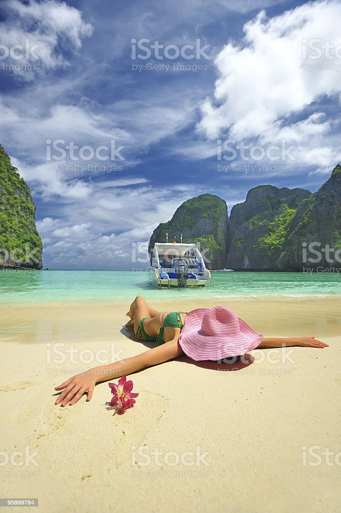 A woman tanning on a tropical beach royalty-free stock photo