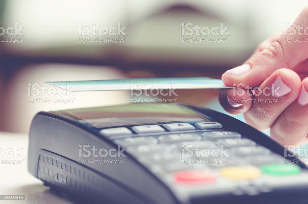 Woman tapping a contactless credit card. stock photo