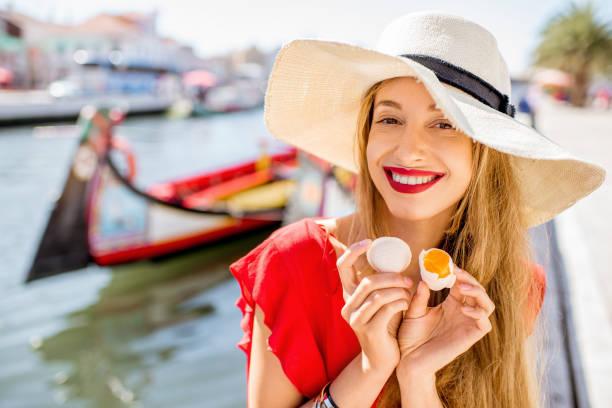 woman tasting portuguese dessert in aveiro city - aveiro imagens e fotografias de stock