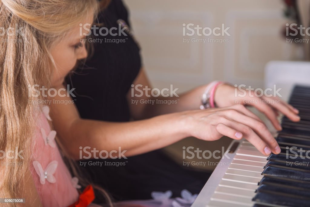 woman teach girl play piano stock photo