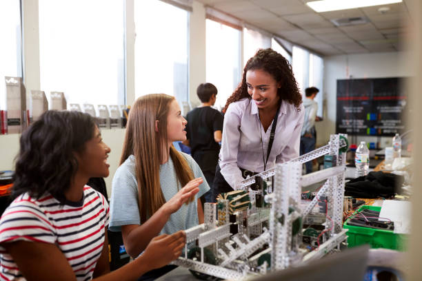 woman teacher with female college students building machine in science robotics or engineering class - high school teacher stock pictures, royalty-free photos & images