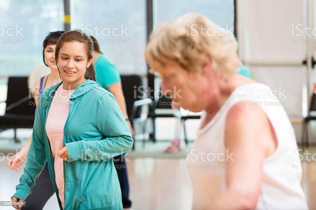 Young Hispanic woman teaches senior Caucasian woman how to line...