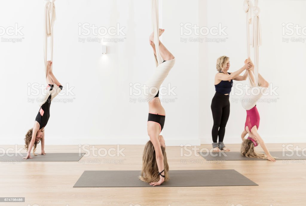 Woman teaching children aerial yoga stock photo