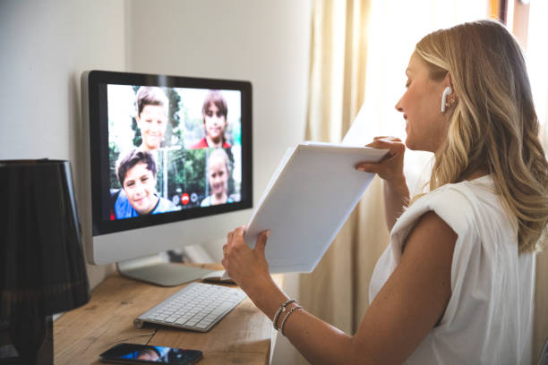 Woman teaching from home to young students stock photo