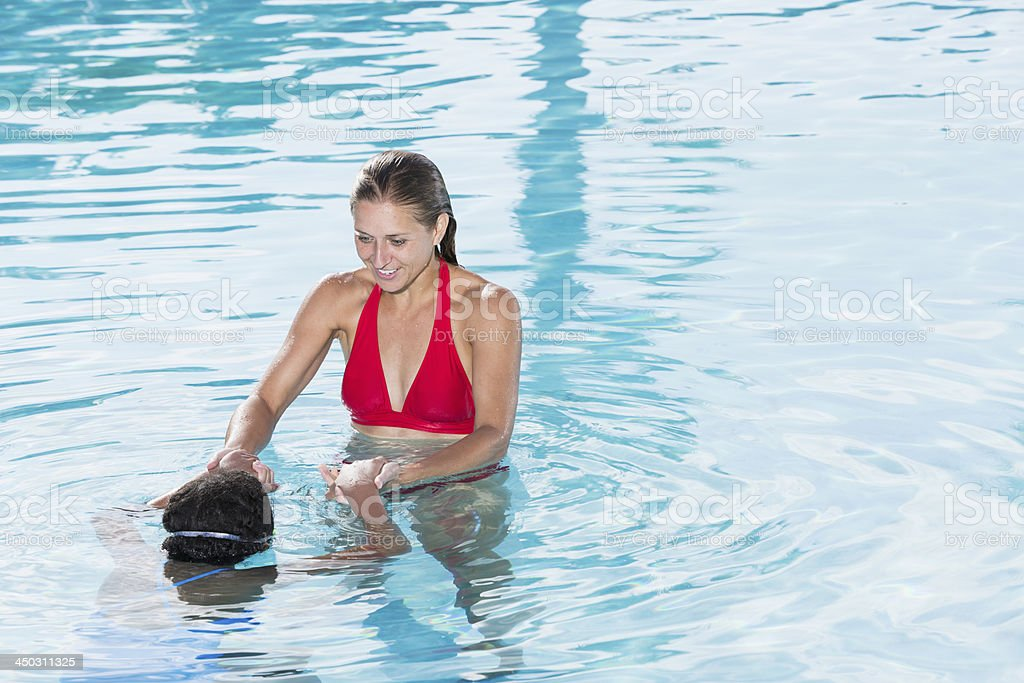 Woman teaching girl to swim stock photo