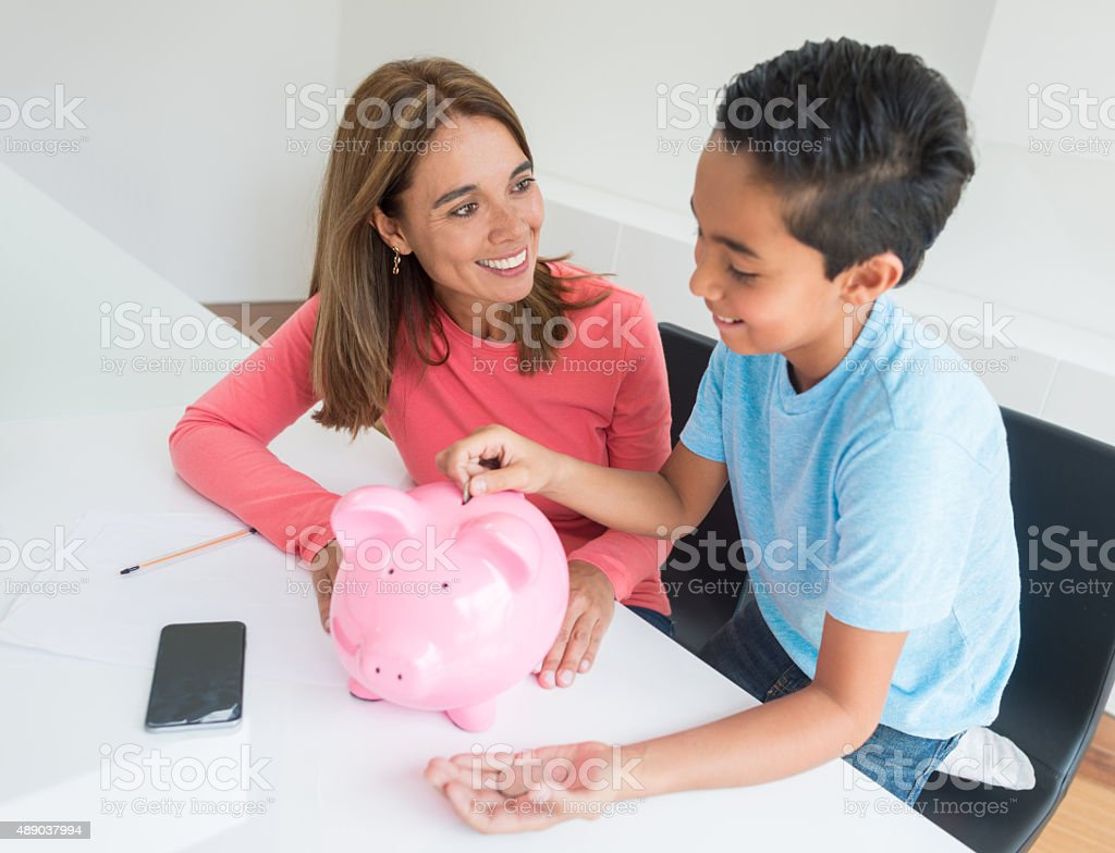 Woman teaching his boy to save money stock photo