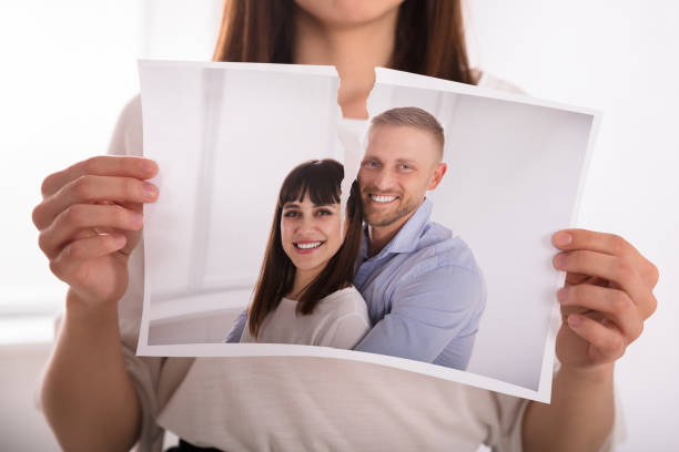 Woman Tearing Photo Of Happy Couple Close-up Of A Woman's Hand Tearing Photo Of Happy Couple former stock pictures, royalty-free photos & images