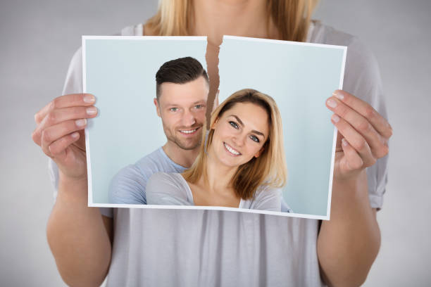 Woman Tearing Photo Close-up Of Woman Tearing Photo Of Smiling Couple former stock pictures, royalty-free photos & images