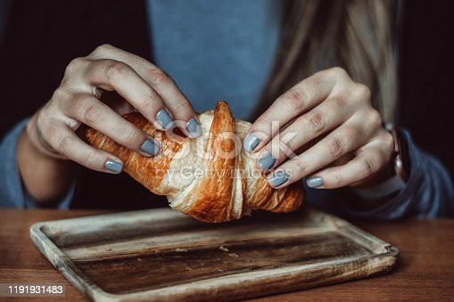 Freshly baked croissant in caffee on humans hands
