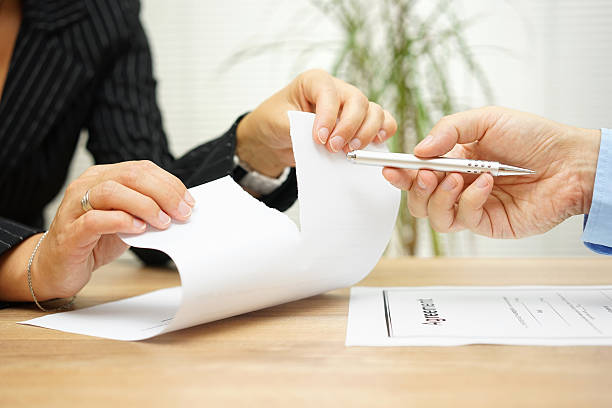 Woman tears agreement documents  in front of agent stock photo