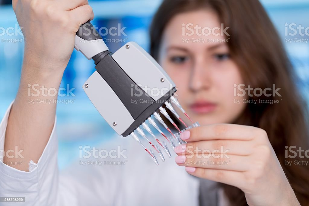 Woman technician with multipipette in genetic laboratory stock photo