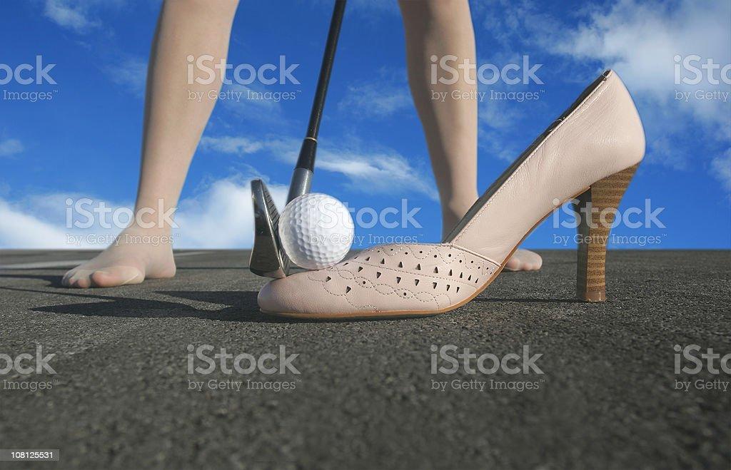 Woman Teeing Off Golf Ball on High Heel Shoe royalty-free stock photo
