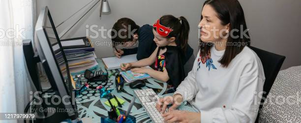 Woman teleworking with her children doing homework picture id1217979979?b=1&k=6&m=1217979979&s=612x612&h=4wzmtual1hjwyxqdnfmmpday2fburbzsg7chsyy4gy0=