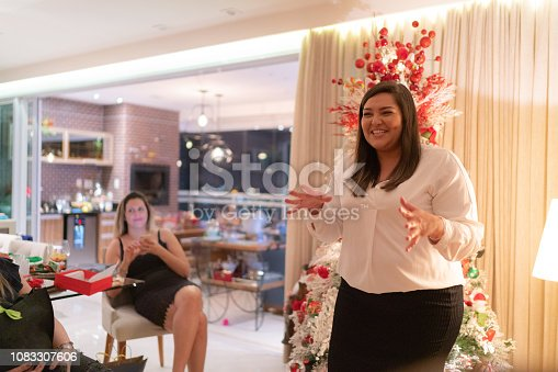 istock Woman telling about surprising friend in a christmas time - Amigo Secreto 1083307606