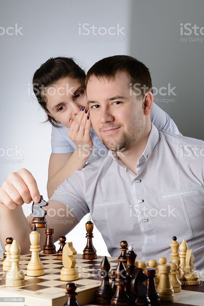 Woman tells a man how to play chess stock photo