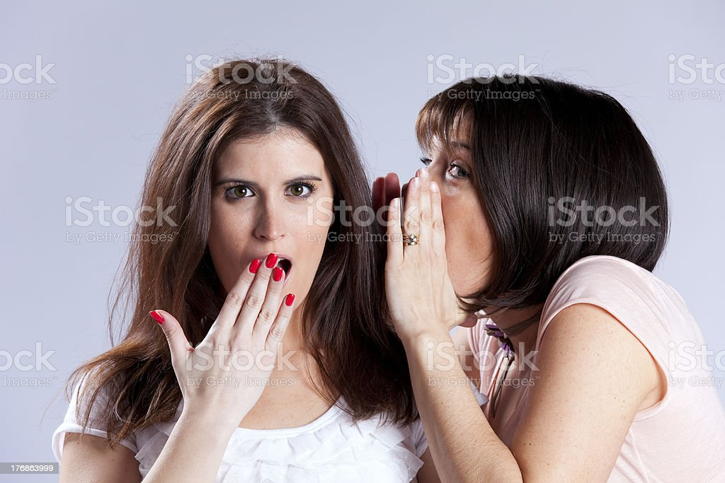Woman tells another a secret, second woman looks shocked stock photo