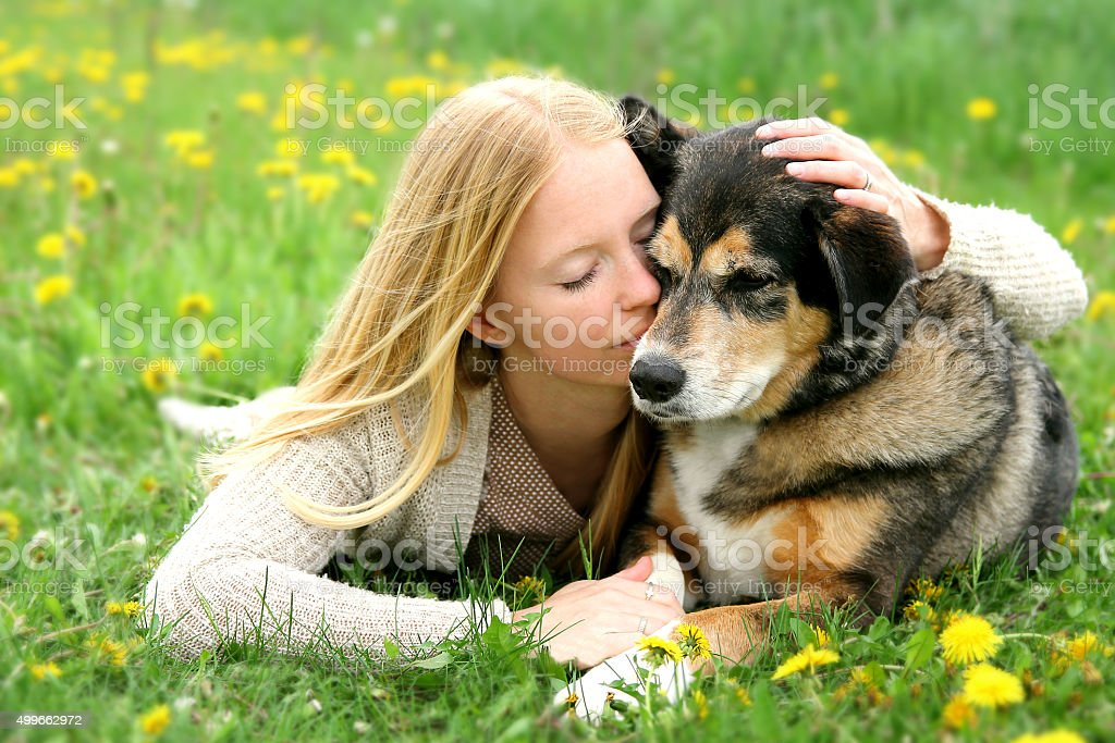 Woman Tenderly Hugging German Shepherd Dog stock photo