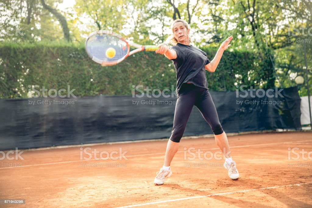 Woman Tennis Player Playing Tennis On Clay Court stock photo