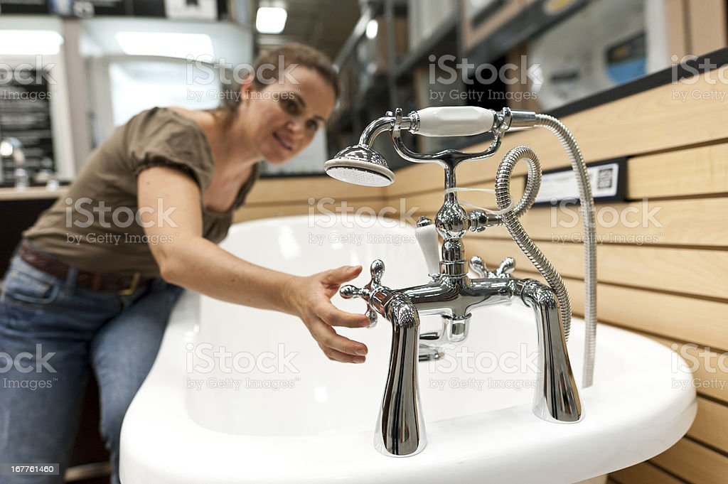 Woman Testing Bathtub Tap In Store stock photo