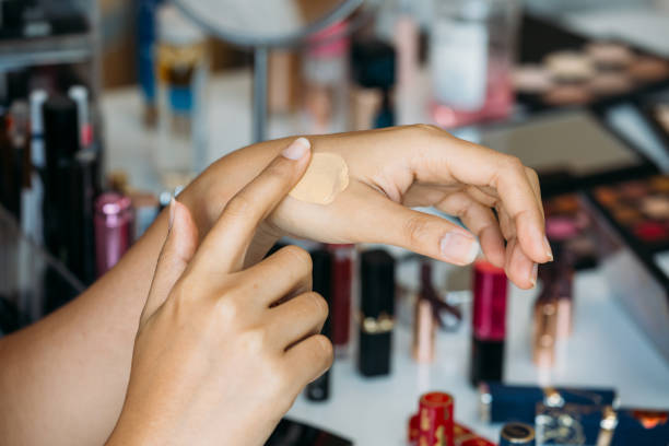 Woman testing concealer on hand near table with cosmetics stock photo
