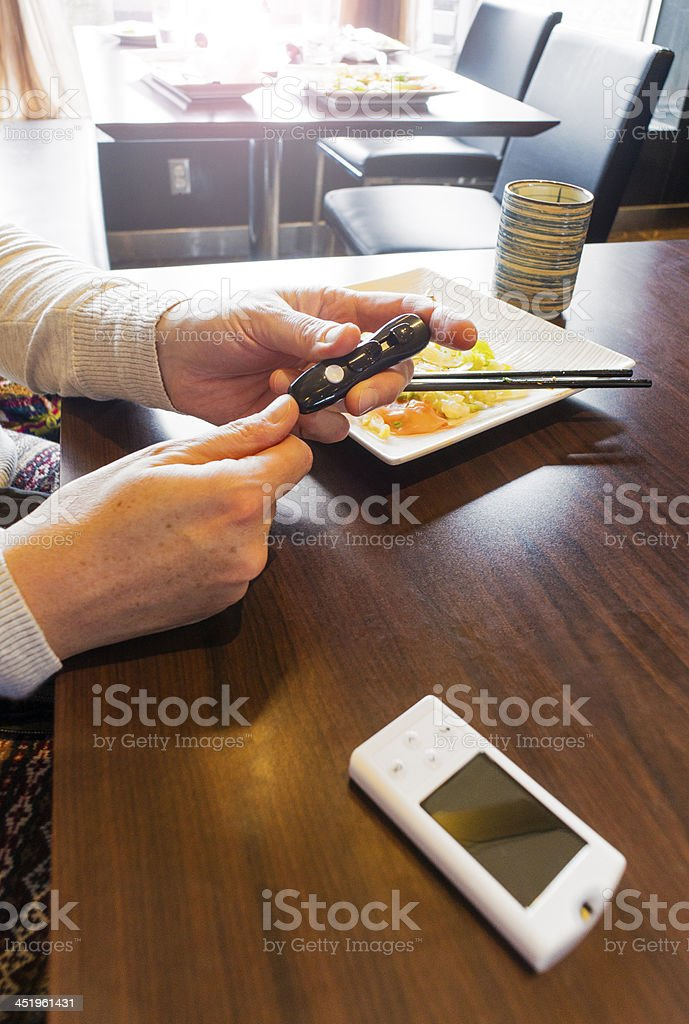 Woman testing her blood glucose level in a restaurant royalty-free stock photo